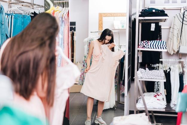 フルショットの女性がドレスを試着 無料写真