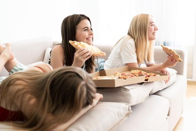 Боком группа друзей, едят пиццу Бесплатные Фотографии