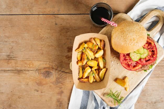 Плоский бургер и картофель фри на деревянной доске Бесплатные Фотографии