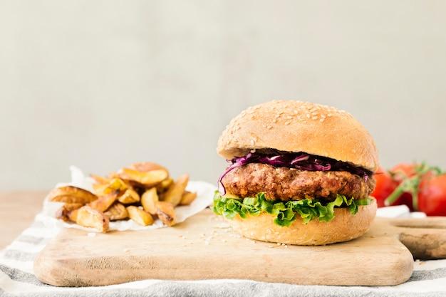 Высокий угол макро бургер с картофелем фри на деревянной доске Бесплатные Фотографии