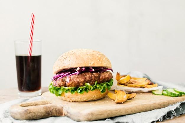 ハンバーガーとフライドポテトの木の板の高角度のクローズアップ 無料写真