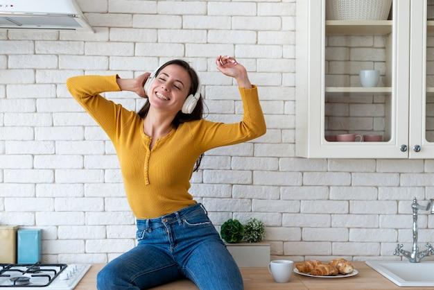 台所で音楽を楽しむ女性 無料写真