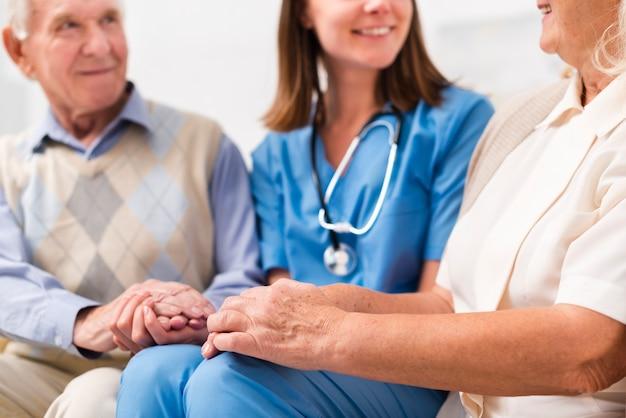 Старик и женщина сидят на желтом диване с медсестрой Бесплатные Фотографии