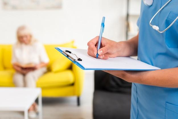 Медсестра пишет на синем буфере обмена крупным планом Бесплатные Фотографии