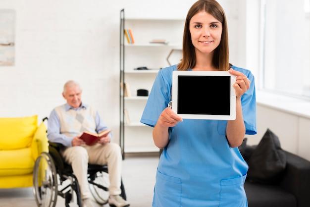 タブレットのモックアップを保持している看護師 無料写真