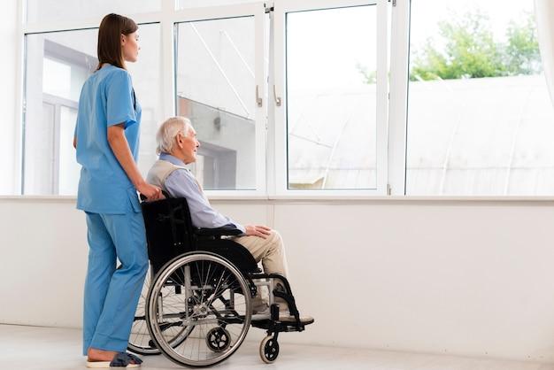 背面ビュー看護師とウィンドウに探している老人 無料写真