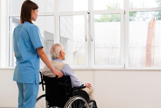 介護者とウィンドウを探している車椅子の老人 無料写真