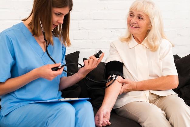 Вид спереди, проверяющий кровяное давление старухи Бесплатные Фотографии