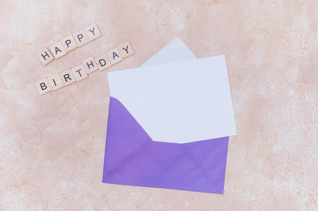 白い誕生日の招待状と紫の封筒のモックアップ 無料写真