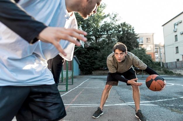 都市コートでバスケットボールをする人 無料写真