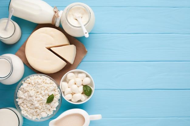 Баночки с молоком и нарезанным сырным колесом Бесплатные Фотографии