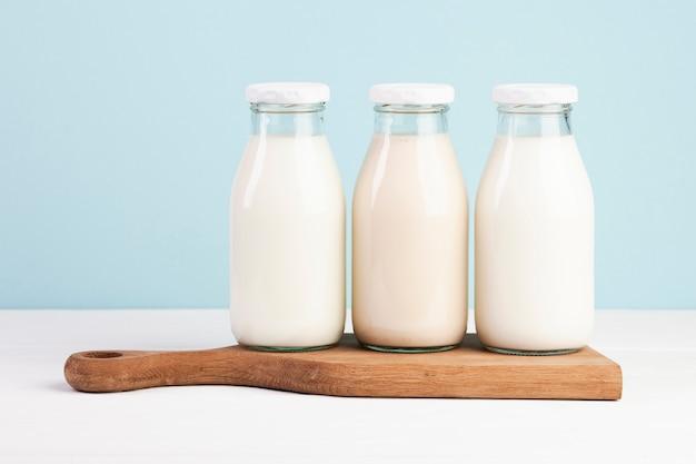Бутылки с молоком на разделочной доске Бесплатные Фотографии