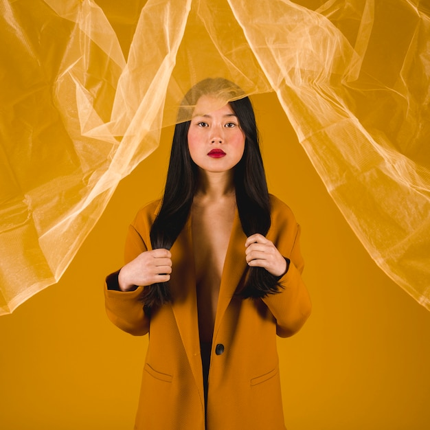 黄色の背景と黄色のコートを着たモデル 無料写真