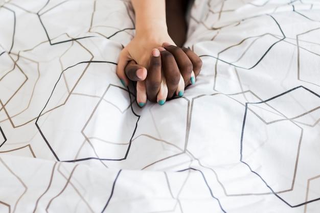 カップルがベッドで手を繋いでいます。 無料写真