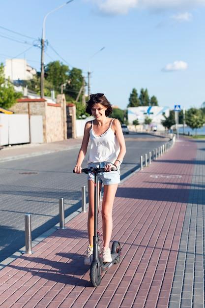 スクーターに乗って笑顔の女性 無料写真