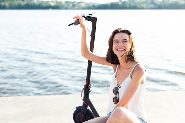 スクーターでポーズをとって正面スマイリー女性 無料写真