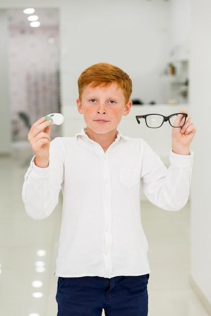 Мальчик держит пластиковый контейнер с контактными линзами и очки, глядя на камеру Бесплатные Фотографии