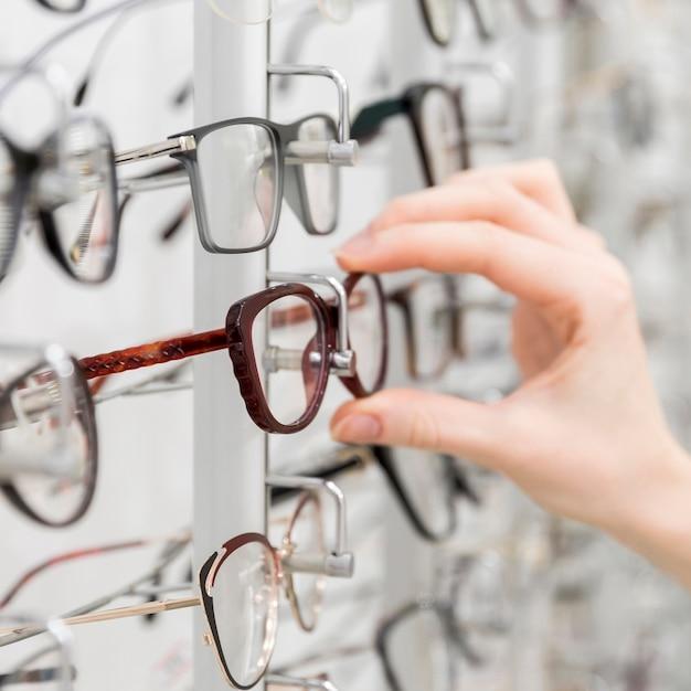 女性の手のクローズアップは、光学店でメガネを選択します 無料写真