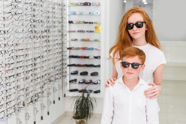 光学ショップで一緒に立っている黒い眼鏡の兄と妹 無料写真