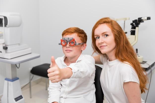 クリニックで若い女性の眼科医と座っているジェスチャーを親指を示す検眼医トライアルフレームを持つ少年 無料写真