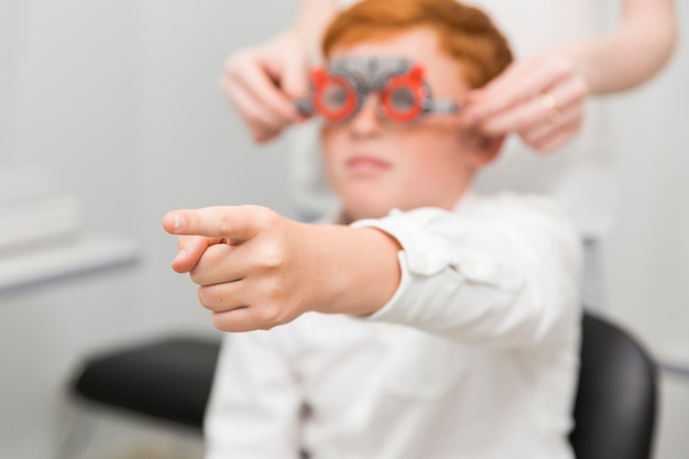 光学クリニックで視力検査をしながら、カメラに向かって人差し指を指している少年 無料写真