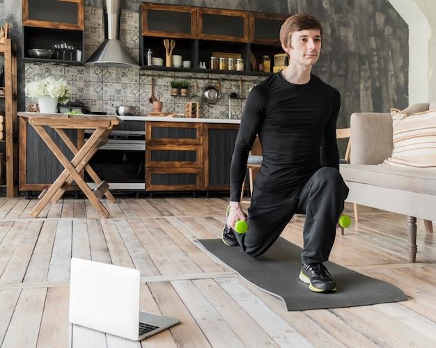 Сосредоточенный человек делает упражнения с гантелями Бесплатные Фотографии