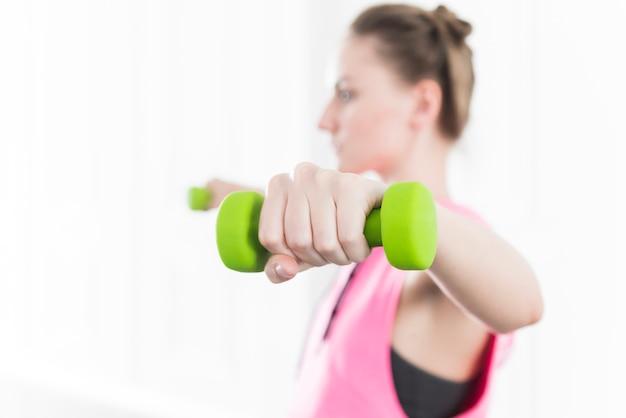 女性のトレーニングと緑色のダンベルを持ち上げる 無料写真