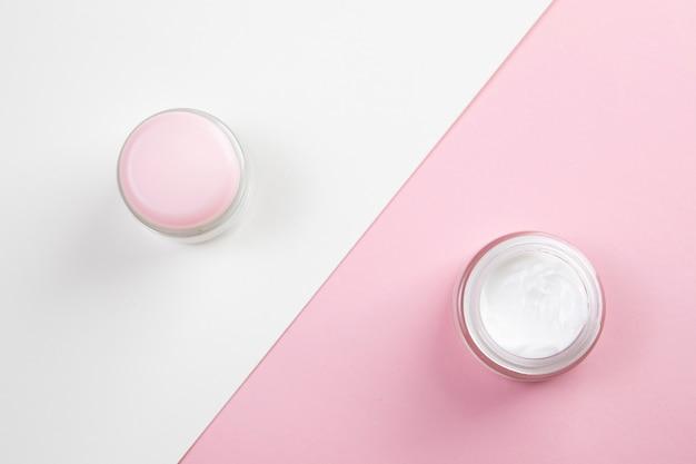 Вид сверху крем для тела на розовом и белом фоне Бесплатные Фотографии
