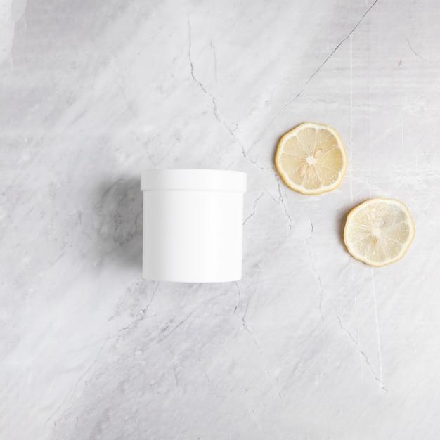大理石の背景にフラットレイアウトボディバターとレモンスライス 無料写真