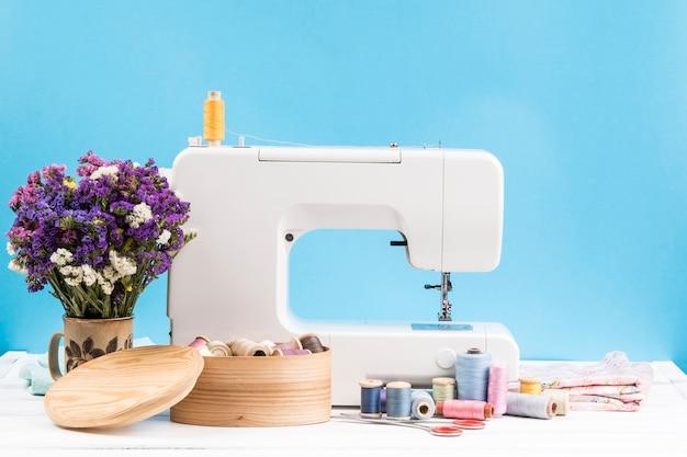 青色の背景に花模様のミシン 無料写真