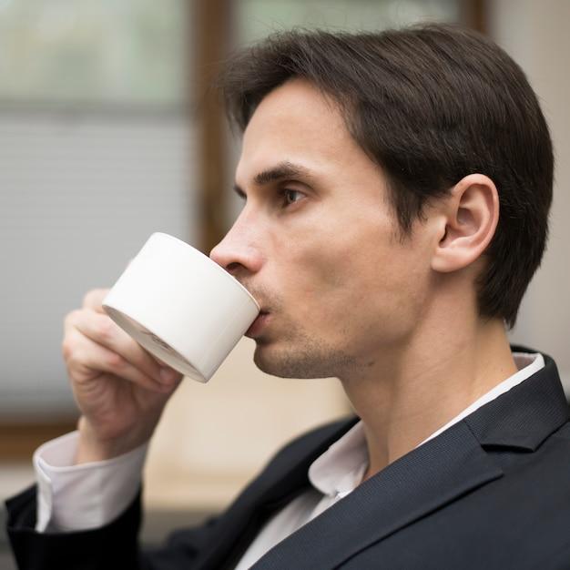 コーヒーを飲む男性のミディアムショット 無料写真