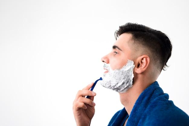 横にハンサムな男彼のひげのクローズアップを剃る 無料写真