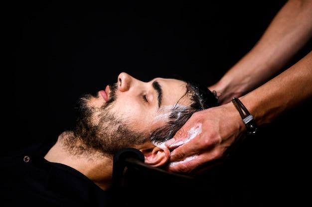 彼の髪を洗った男の側面図 無料写真