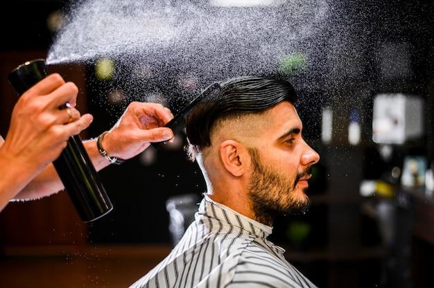 Вид сбоку парикмахера-распылителя волос его клиента Бесплатные Фотографии