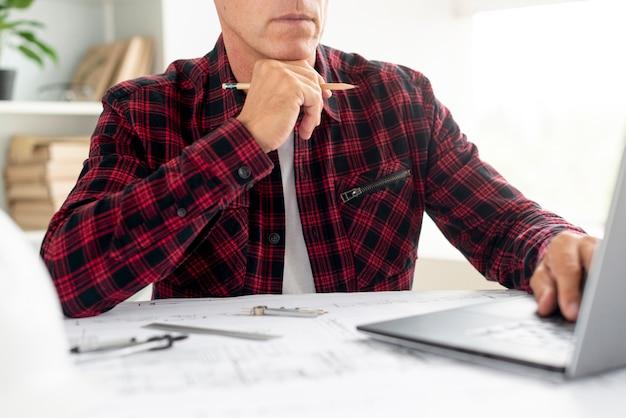 Человек смотрит на архитектурный проект на ноутбуке Бесплатные Фотографии