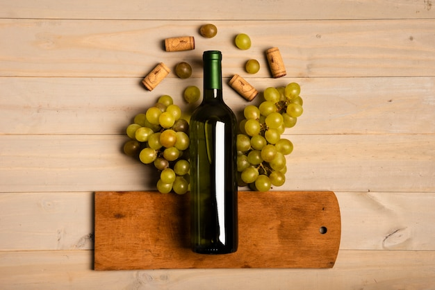 ブドウの近くのまな板の上に置いたワインのボトル 無料写真
