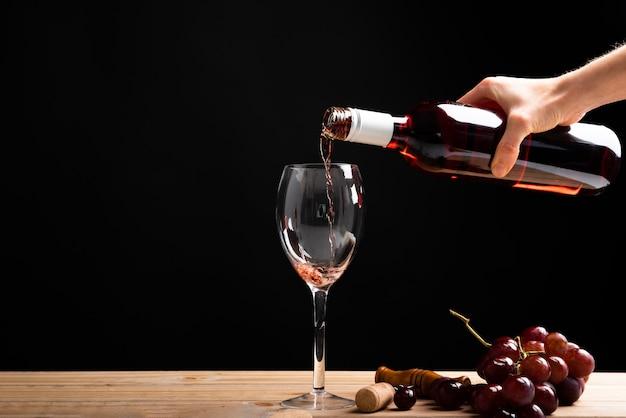 Вид спереди красное вино наливают в бокал Бесплатные Фотографии