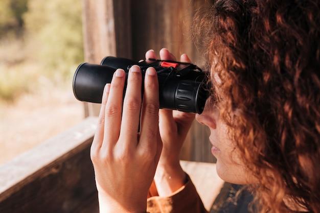 Макро рыжий женщина смотрит в бинокль Бесплатные Фотографии