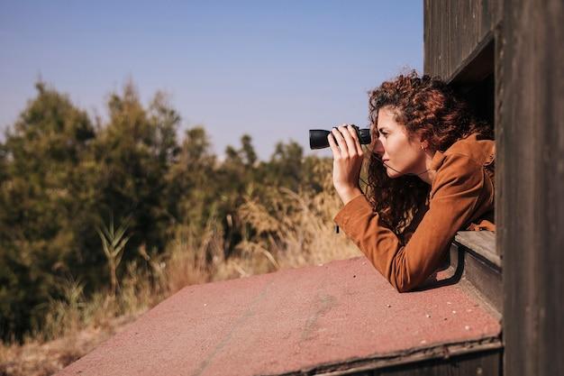 Боком рыжая женщина смотрит в бинокль Бесплатные Фотографии