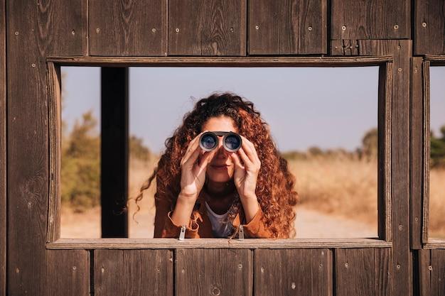 Вид спереди рыжий женщина смотрит в бинокль Бесплатные Фотографии