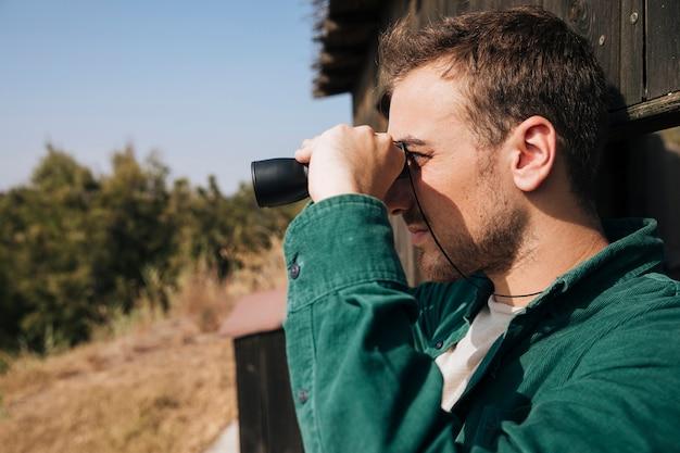 Боком человек смотрит в бинокль Бесплатные Фотографии