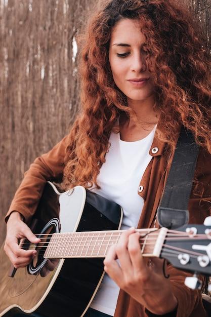 ミディアムショットの女性がギターを弾く 無料写真