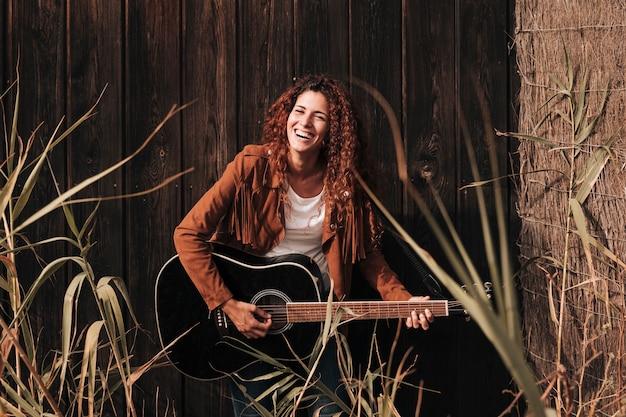 フロントビュー幸せな女、ギターを弾く 無料写真