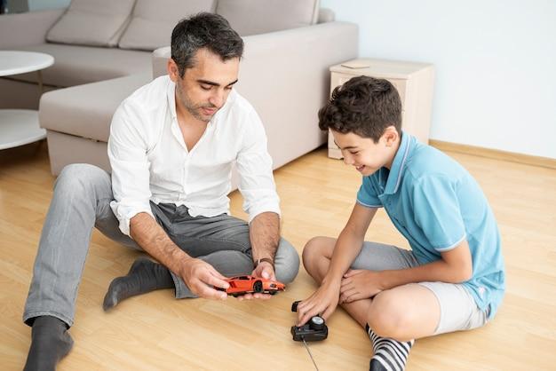 フロントビュー父と子、電気自動車で遊ぶ 無料写真
