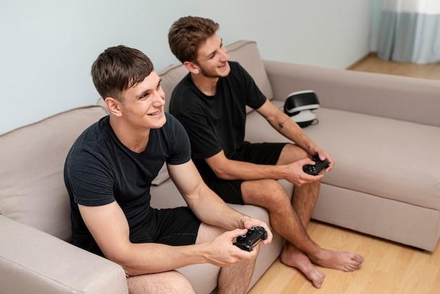 Боковой вид мальчики играют на диване Бесплатные Фотографии