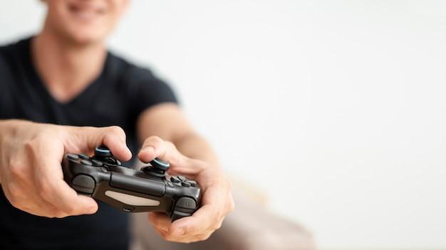Крупным планом размытым парень держит контроллер Бесплатные Фотографии