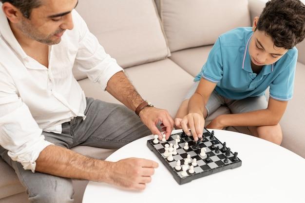 Высокий угол взрослый и ребенок играет в шахматы Бесплатные Фотографии