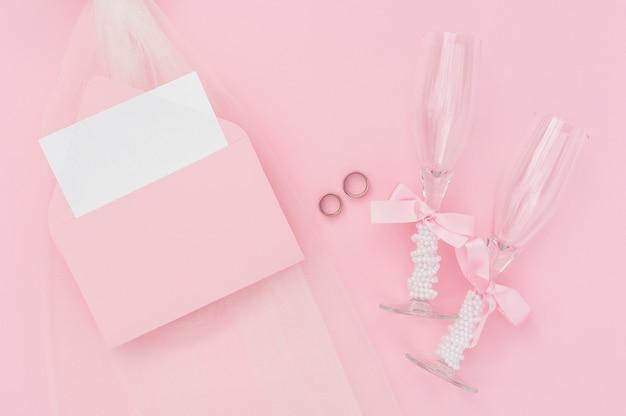 結婚式の招待状の横にあるシャンパングラス 無料写真