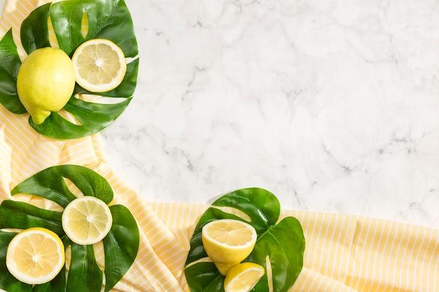 Симпатичная композиция лимонов на листьях монстера Бесплатные Фотографии