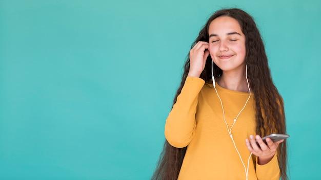 コピースペースで音楽を聴いている女の子 無料写真